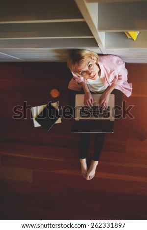 Top view young female freelancer busy working on laptop computer while leaning on home bookshelf sitting on the floor, charming business woman working from home while having breakfast, look to camera - stock photo
