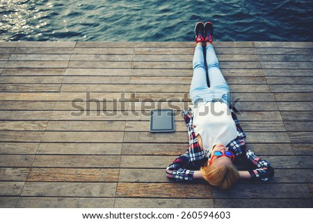 Top view young woman lying on a wooden jetty enjoying the sunshine,tourist girl in bright glasses lying on jetty by river, vintage photo of relaxing young woman in nature with tablet, cross process - stock photo