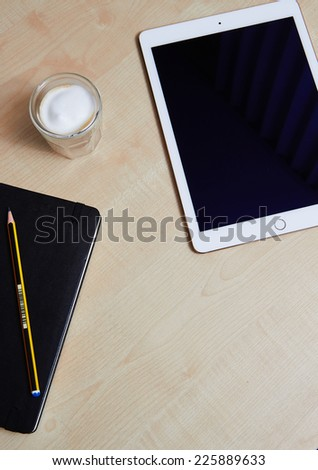 Top views showing iPad Air 2 with touch id on wooden desk and a coffee - stock photo
