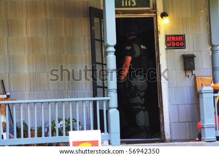 TOPEKA, KS - JULY 10: The Topeka police S.W.A.T. and Hostage Rescue teams respond to a home where a man barricaded himself in his home, threatening harm to himself on July 10, 2010 in Topeka, KS. - stock photo