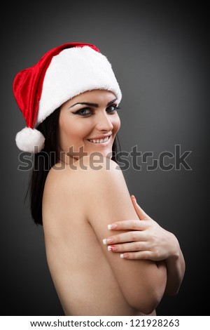 Topless sexy Santa girl with red hat on grey background - stock photo