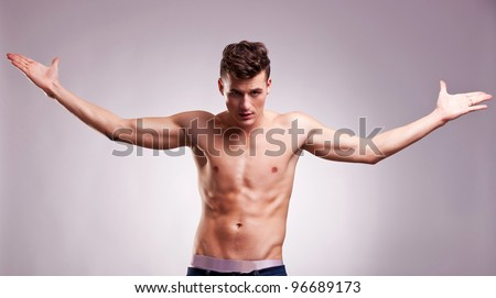 topless young fashion model with his hands in the air at his sides on gray background. muscular young man with arm outstretched - stock photo