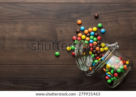 topple over glass jar full of colorful sweets - stock photo