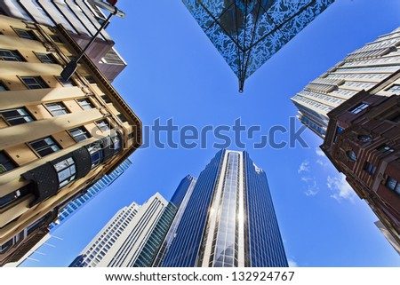 tops and roofs of skyscrapers mixtures with old-fashioned historical buildings in CBD of big city sunny day blue sky between buildings perspective view bottom-up - stock photo