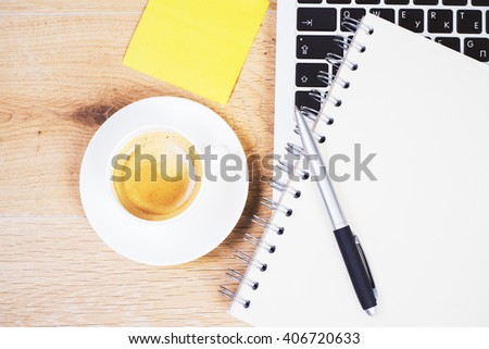 Topview of table with keyboard, coffee, notepad and yellow stickers - stock photo