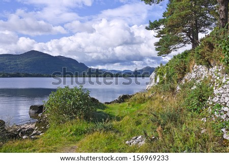 Torc Mountain and the Eagle's Nest Rock from a grassy path by the shore of Lough Leane, the Lower Lake, Killarney, Ireland. - stock photo