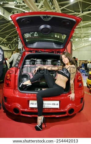 TORINO, ITALY - FEBRUARY 15, 2015: Sensual tattooed hostess posing inside a trunk of a Mini Cooper Countryman with personalized car power audio system at Expo Tuning Torino on February 15, 2015 - stock photo