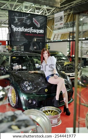 TORINO, ITALY - FEBRUARY 15, 2015: special version of Mini Cooper S John Cooper Works edition tuned car with sensual and young model with high heels posing at Expo Tuning Torino on February 15, 2015 - stock photo