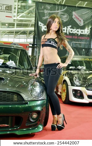 TORINO, ITALY - FEBRUARY 15, 2015: Young and sensual tattooed hostess or pinup with high heels, posing near a Mini Cooper S John Cooper Works tuned cars at Expo Tuning Torino on February 15, 2015 - stock photo