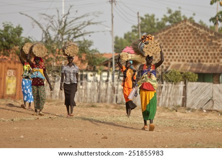 TORIT, SOUTH SUDAN-FEBRUARY 20, 2013: Unidentified women carry heavy loads on their heads in South Sudan - stock photo