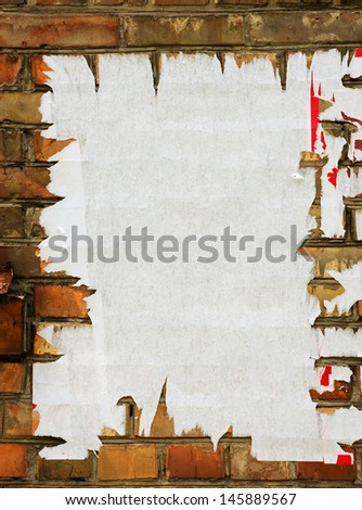 Torn advertisement on the brick wall as background - stock photo