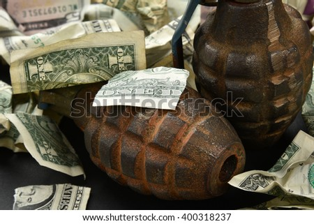 torn and crumpled money and hand grenades indicating an explosive economy and economic destruction - stock photo