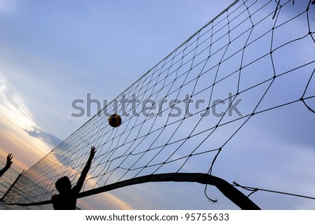 Torn beach volleyball net at tropical beach during sunset. - stock photo