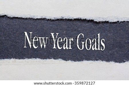 Torn Blue Paper and white background with new year goals words written on. - stock photo