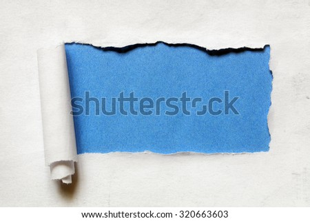 Torn paper over a blank blue background for message - stock photo