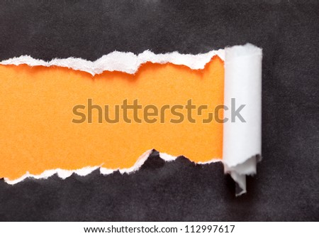 Torn paper with orange space for your message. Black background - stock photo