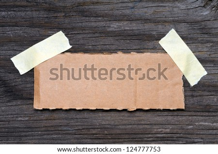 Torn piece of cardboard on wooden background - stock photo