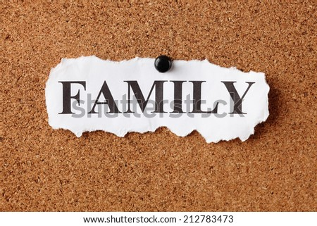 "Torn piece of paper with the word ""Family"" on corkboard (bulletin board). Close-up. - stock photo"