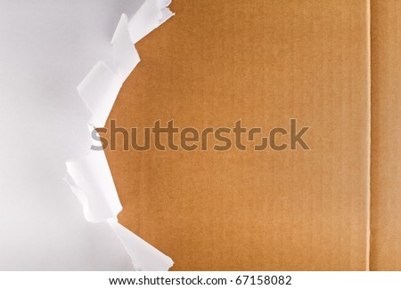 Torn wrapping paper revealing brown cardboard box - stock photo