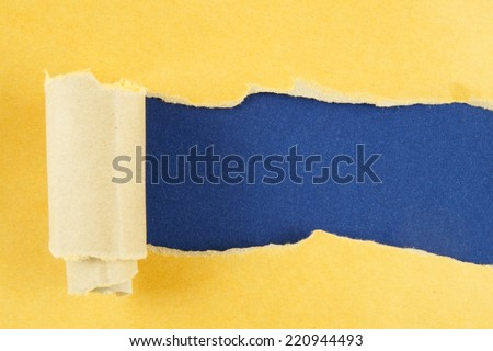 Torn yellow paper with blue background  - stock photo