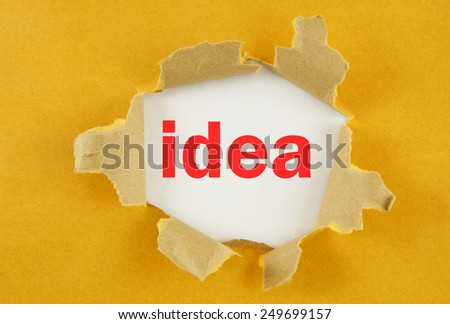 Torn yellow paper with word idea on white background  - stock photo