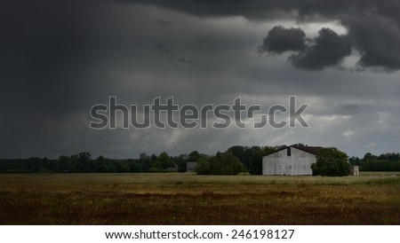 Tornado storm clouds above the shed in the countryside - stock photo