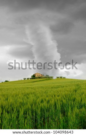 tornado surrounds the house on the hill - stock photo