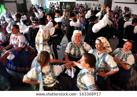 TOROCKO (RIMETEA) - AUG 30: Dancers in traditional Slovak clothes participate in the Hungarian folklore festival during the Rimetea Village Days. On August 30, 2013 in Torocko, Transylvania, Romania - stock photo
