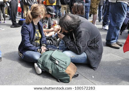 TORONTO - APRIL 20:  A couple lighting their pots during the annual marijuana 420 event at Yonge & Dundas Square  on April 20  2012 in Toronto, Canada. - stock photo