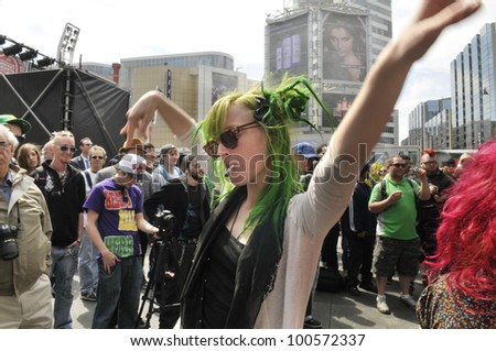 TORONTO - APRIL 20: A marijuana legalization supporter dancing on live music while smoking weed  during the annual marijuana 420 event at Yonge & Dundas Square  on April 20  2012 in Toronto, Canada. - stock photo