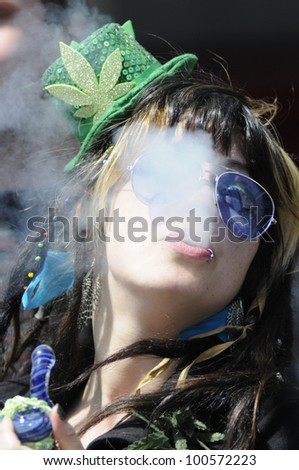TORONTO - APRIL 20:  A Marijuana smoker blowing off smoke  during the annual marijuana 420 event at Yonge & Dundas Square  on April 20  2012 in Toronto, Canada. - stock photo