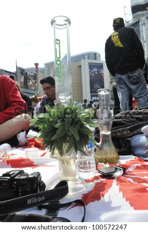 TORONTO - APRIL 20:   Bongs surrounded by marijuana  activists during the annual marijuana 420 event at Yonge & Dundas Square  on April 20  2012 in Toronto, Canada. - stock photo