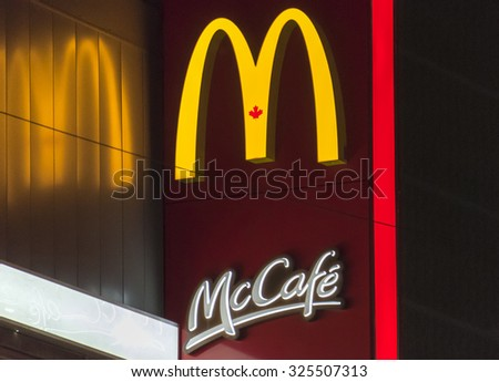 TORONTO,CANADA-AUGUST 12,2015: The McDonald's logo and signage of McCafe outside the McCafe restaurant in Toronto. McCafe is a coffee-house-style food and drink chain, owned by McDonald's. - stock photo