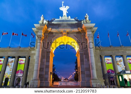 TORONTO, CANADA - 20 AUGUST 2014: The outside of the Canadian National Exhibition Arch during the CNE event. In the distance rides can be seen. - stock photo