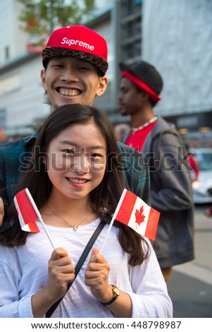 TORONTO,CANADA-JULY 1,2016:Canada Day people: Asian couple enjoying the music and events in Dundas Square.Canada Day  is the national day of Canada and a federal statutory holiday - stock photo