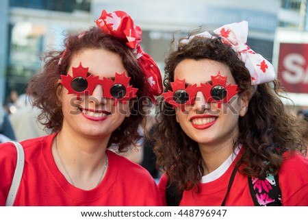 TORONTO,CANADA-JULY 1,2016:Canada Day people: Friends wearing the Canadian colors and enjoying the music in Dundas Square..Canada Day  is the national day of Canada and a federal statutory holiday - stock photo