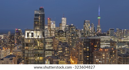 TORONTO, CANADA - JULY 24, 2015: Night view from above of  Downtown Toronto skyscrapers and CN Tower apex at the background. - stock photo