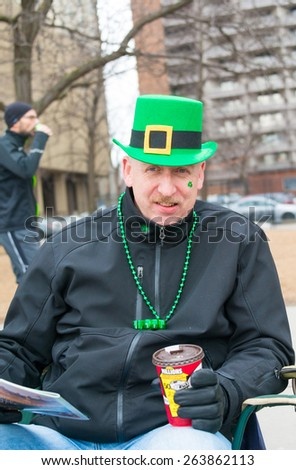 TORONTO,CANADA-MARCH 15,2015:General public enjoying a traditional Canadian Tim Horton's coffee while watching the 28th edition of the St. Patrick's Day Parade the fourth largest in the world. - stock photo