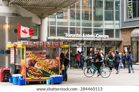 TORONTO,CANADA-MAY 17,2015: Hot dog stand with Canadian Flag at the entrance of Eaton Centre in Summer.City council will allow food cart vendors to sell more than hot dogs and sausages.  - stock photo