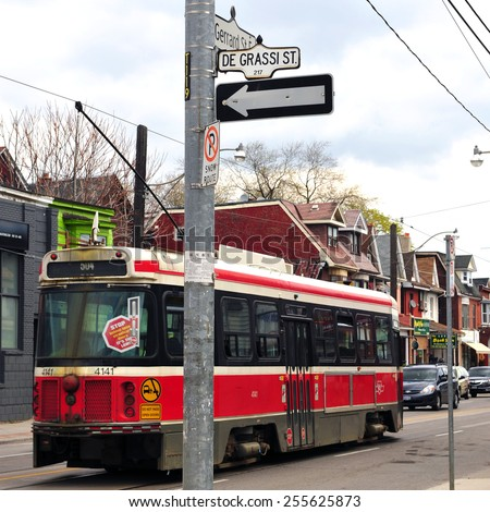 TORONTO, CANADA - MAY 7, 2011: Toronto Street car drives by Degrassi Street sign. The popular Canadian TV franchise now known simply as Degrassi started out as The Kids of Degrassi Street.   - stock photo