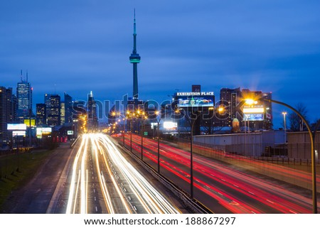 TORONTO, CANADA - 22ND APRIL 2014: Light trails on the Gardiner Expressway leading up to the CN Tower and Downtown Toronto - stock photo
