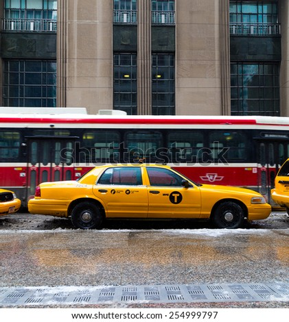 TORONTO, CANADA - 22ND FEBRUARY 2015: A New York City Taxi in downtown Toronto during the day. A Streetcar can be seen behind it - stock photo
