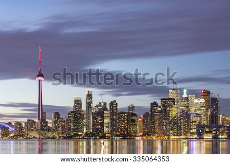 TORONTO, CANADA - NOVEMBER 02, 2015: Downtown Toronto skyline with the CN Tower apex and the Financial District skyscrapers - illuminated at dusk. - stock photo