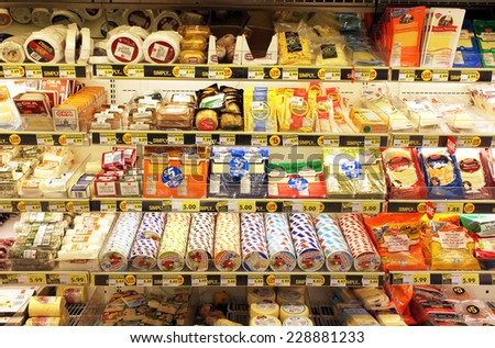 TORONTO, CANADA - OCTOBER 31, 2014: Different types of cheese on shelves in a grocery store. Hundreds of types of cheese are produced by various countries with different styles, textures and flavors. - stock photo