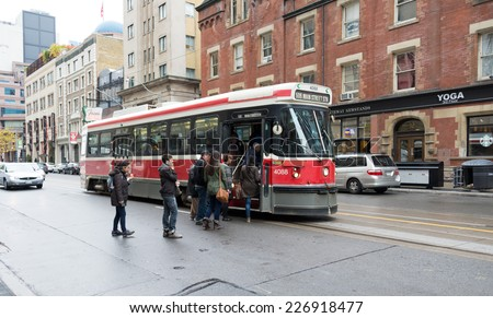 TORONTO,CANADA-OCTOBER 24,2014:People getting on a Toronto streetcar, this old Bombardier streetcars will be replaced in a lapse of five years by the new Bombardier Flexity Outlook - stock photo