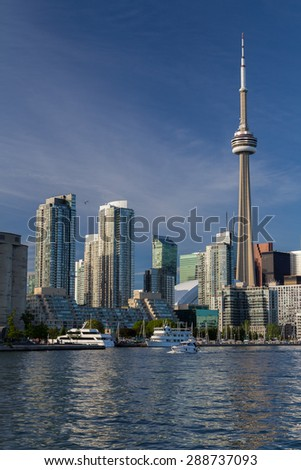 TORONTO, CANADA - 7TH JUNE 2015: The CN Tower, condos, office buildings in Toronto along the waterfront. Boats can also be seen. - stock photo