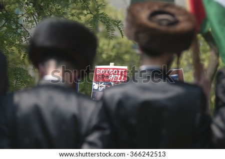 "TORONTO-JULY 11: A ""Boycott Israel"" sign being waved in front two Jewish Rabbis during the Al-Quds day rally on July 11, 2015 in Toronto,Canada. - stock photo"