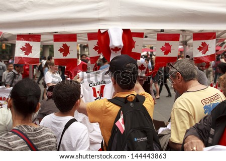TORONTO - JULY 1, People buying apparel with canadian symbols to celebrate Canada Day  at Yonge Dundas square   July 1, 2013 in Toronto, Canada.   - stock photo