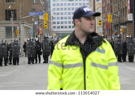 TORONTO-JUNE 26:  A police officer standing on the first line of control while other riot police officers stand on the second line during the G20 Protest on June 26, 2010 in Toronto, Canada. - stock photo