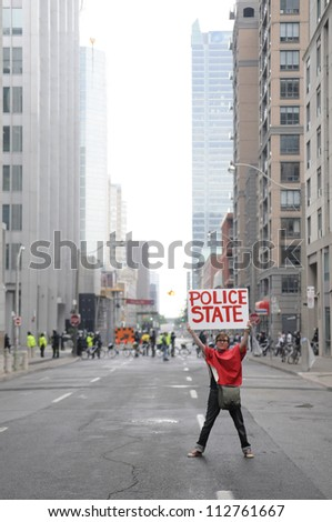"TORONTO-JUNE 26:  A protester holding a sign which says that this sate has become a ""police state"" right in front of a line of riot police during the G20 Protest on June 26 2010 in Toronto, Canada. - stock photo"